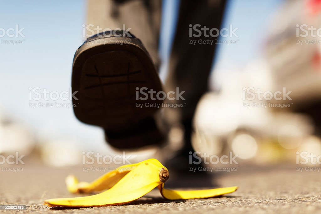 Painful accident about to happen. Foot approaching banana peel. stock photo