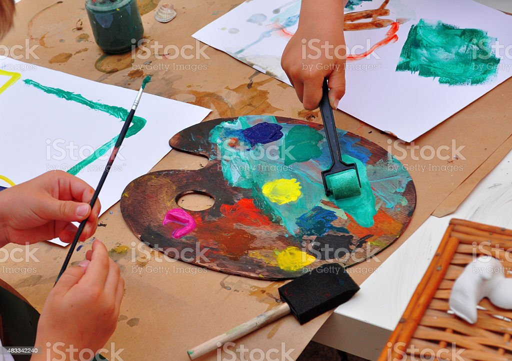 Paint Art Palette, brushes and children hands stock photo