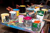 Paint bottles, brushes and paint cans