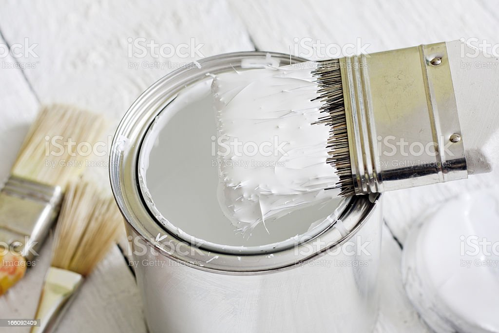 Paint brush and can on white planks royalty-free stock photo
