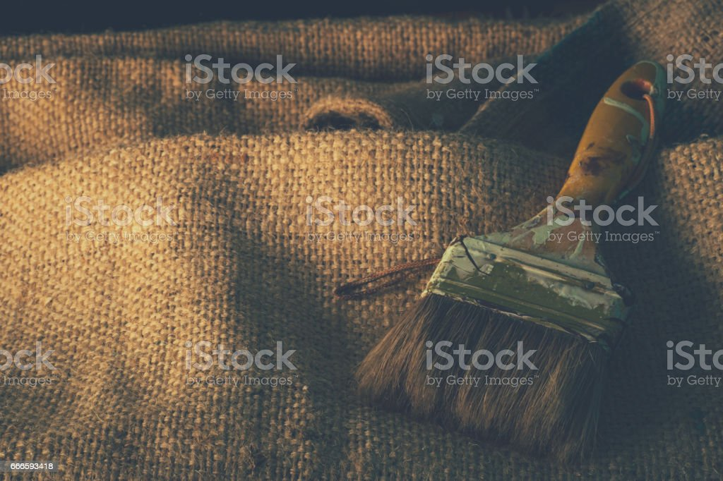 Paint brush on old burlap or sackcloth texture background with copy space. stock photo