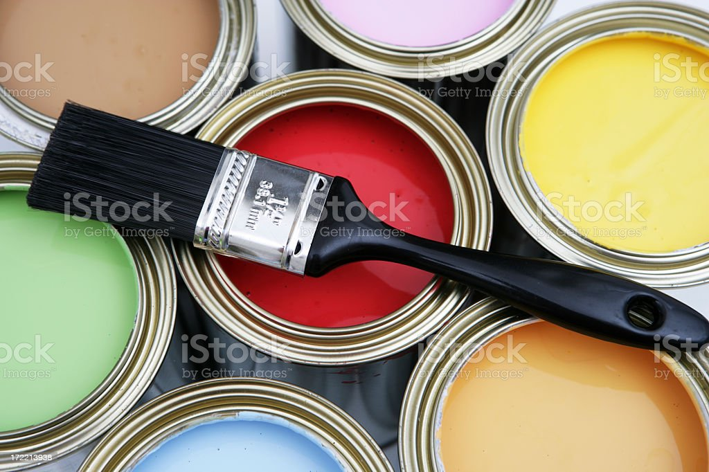 Paint brush resting on open paint buckets royalty-free stock photo