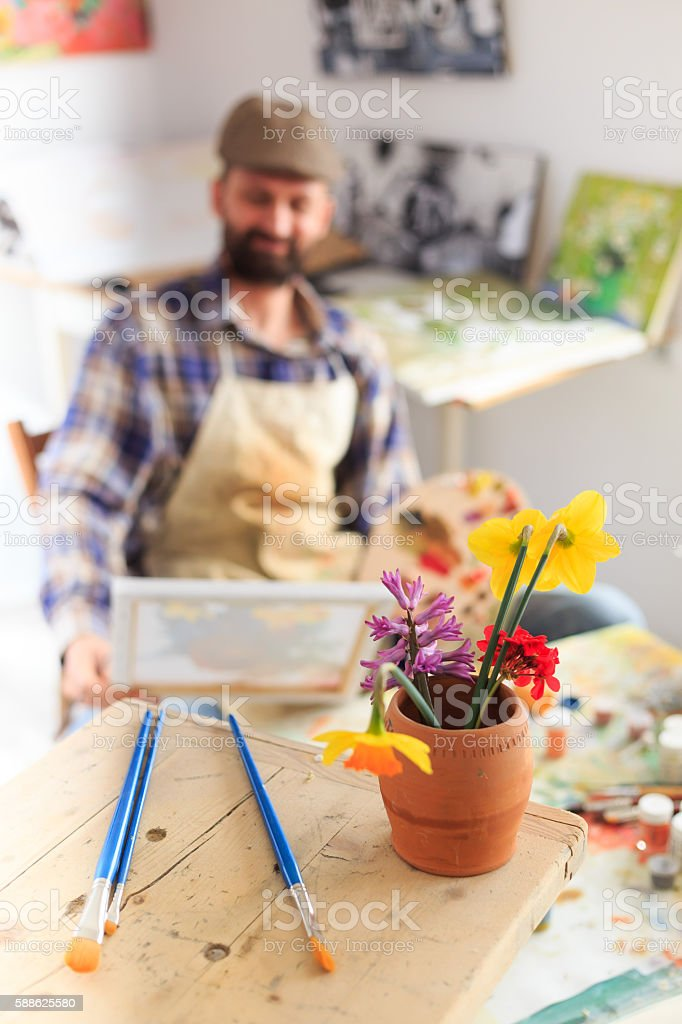 Paint brushes and vase with flowers in painter's workshop stock photo