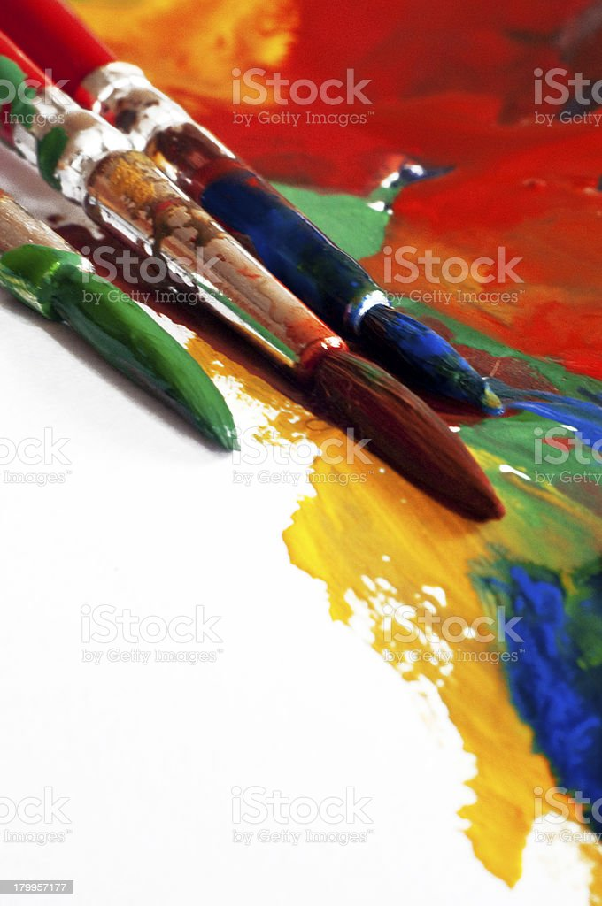 Paint brushes covered with paint on top of painting stock photo