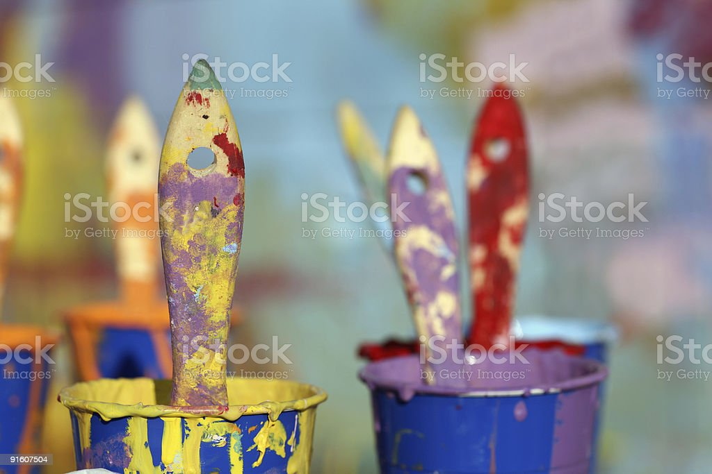 Paint brushes in cups of multi color paints royalty-free stock photo