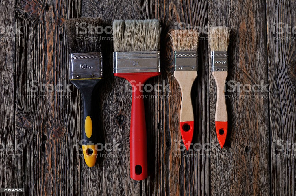 paint brushes lying on painted wooden boards stock photo