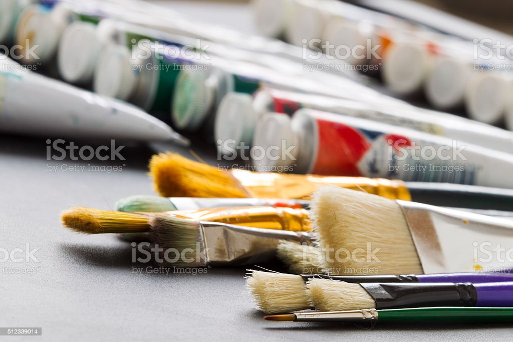 Paint brushes on the background of tubes of paint stock photo