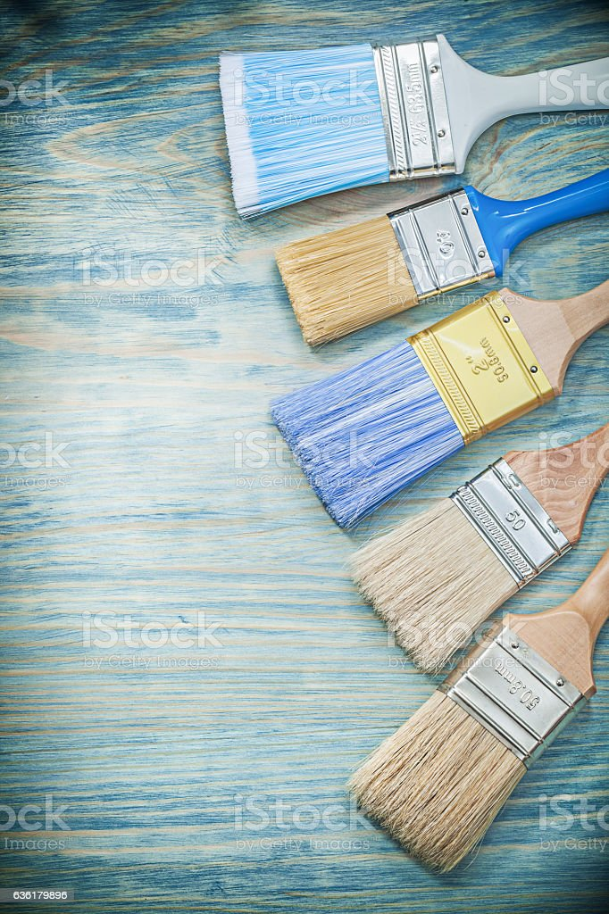 Paint brushes on wooden board vertical view construction concept stock photo