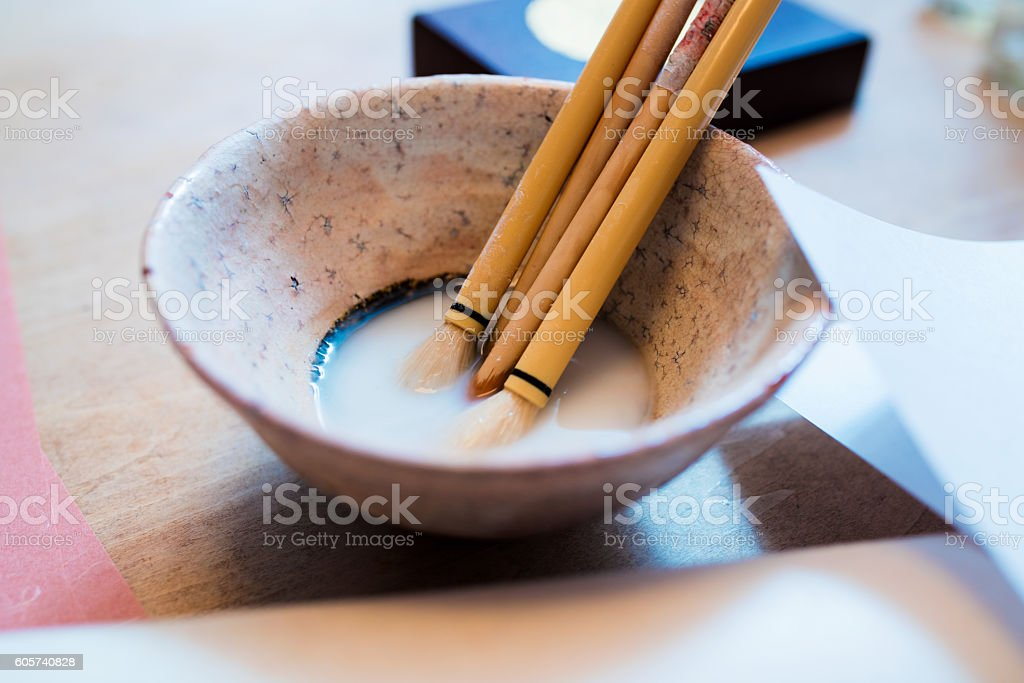 Paint brushes resting in a bowl stock photo