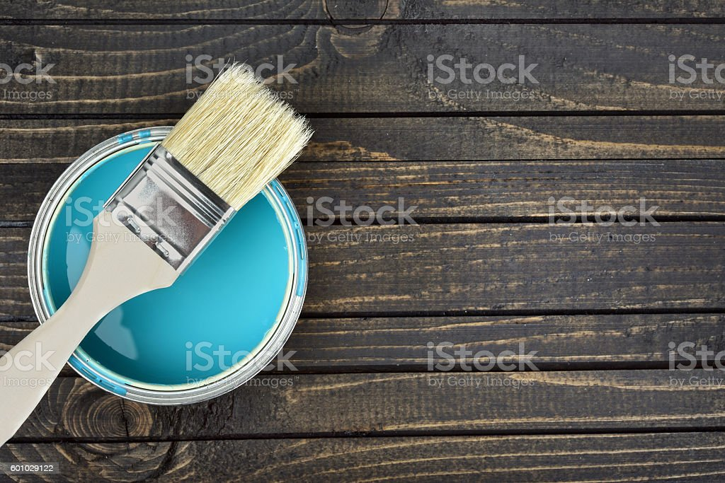 Paint bucket and brush on table stock photo