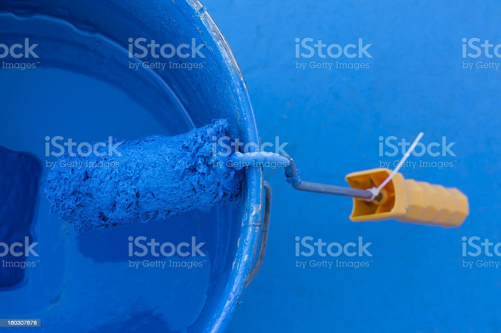 Paint can with blue color and orange roller royalty-free stock photo
