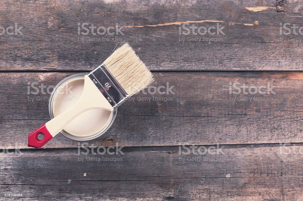 paint can with paintbrush on old wooden background stock photo