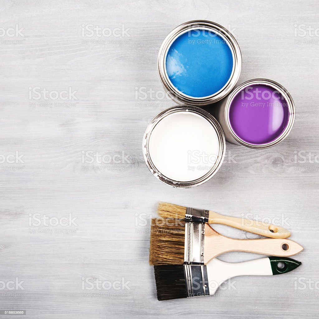 Paint cans and colored brushes on white background stock photo