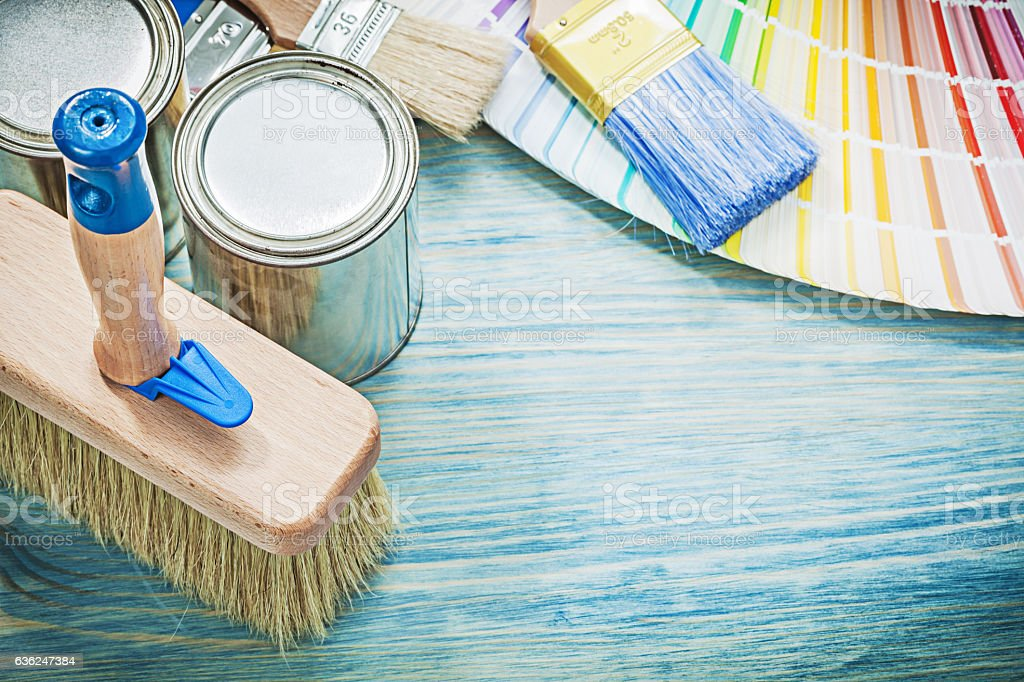Paint cans brushes colour sampler on wooden board construction conc stock photo