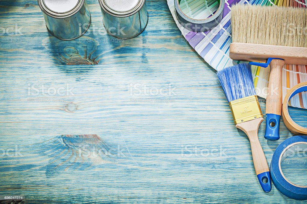 Paint cans brushes pantone fan adhesive tape on wooden board stock photo