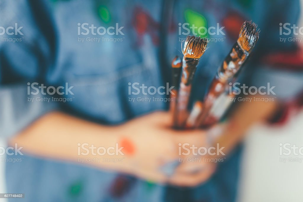 Paint covered hands of an artist holding paitnbrushes stock photo