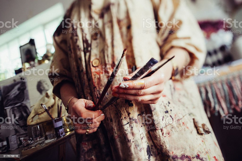 Paint covered hands of an artist in smock holding paitnbrushes stock photo