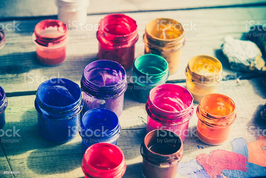 paint jars on a wooden surface stock photo