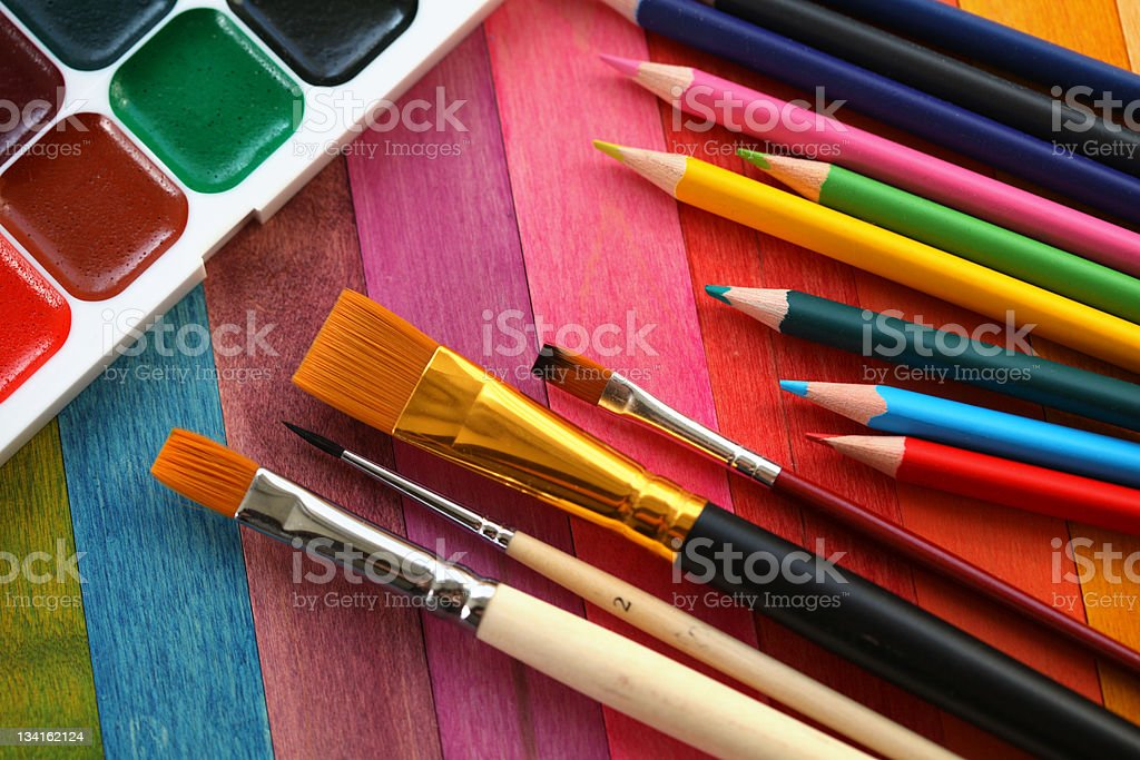 Paint next to an assortment of paintbrushes and pencils royalty-free stock photo
