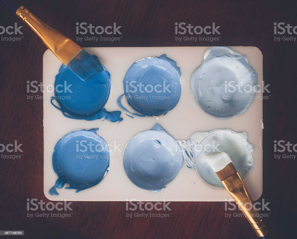 Paint palette with paint colors in various shades of blue stock photo