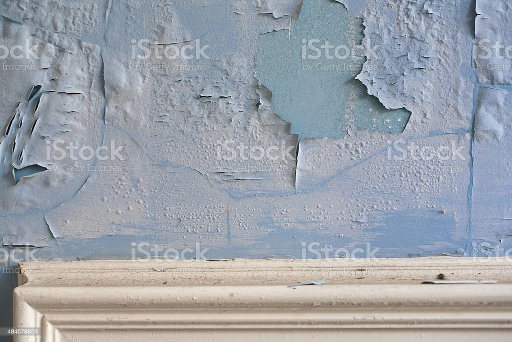 Paint peeling on an old plaster wall above moulding stock photo
