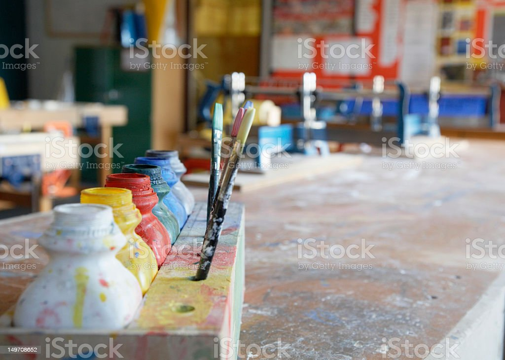 Paint pots and brushes on paint spattered worktop, close-up royalty-free stock photo