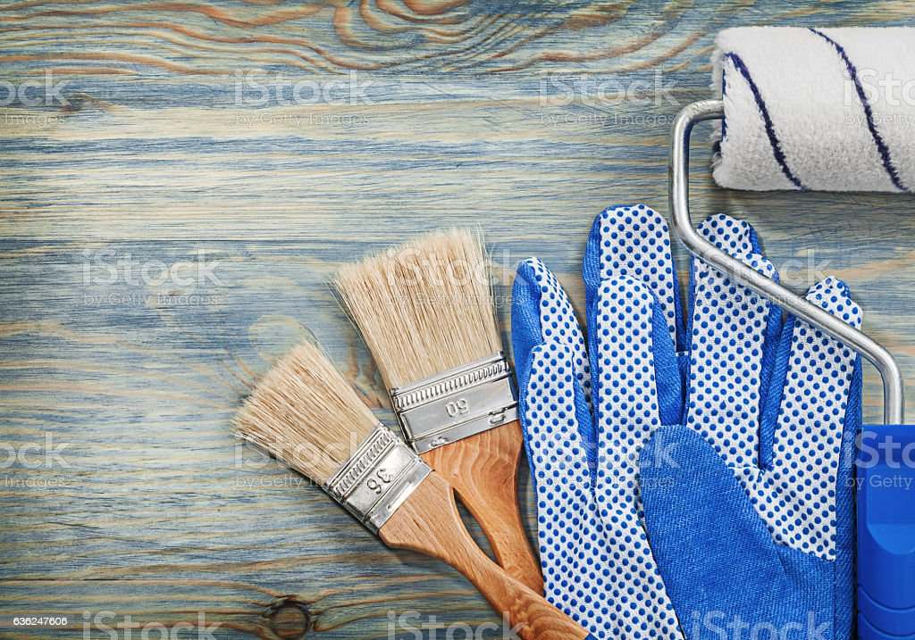 Paint roller brushes working gloves on wooden board construction stock photo