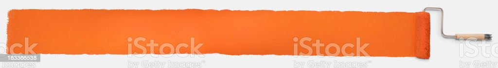 Paint roller making a long orange paint stripe stock photo