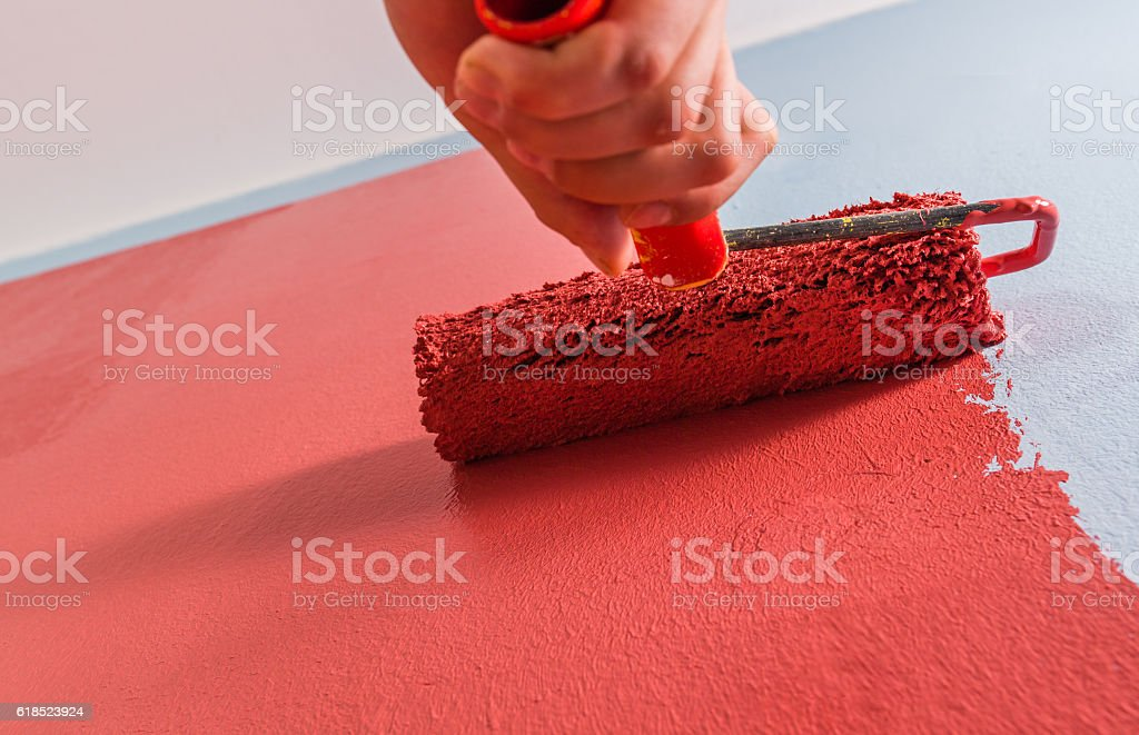 Paint roller on the wall stock photo