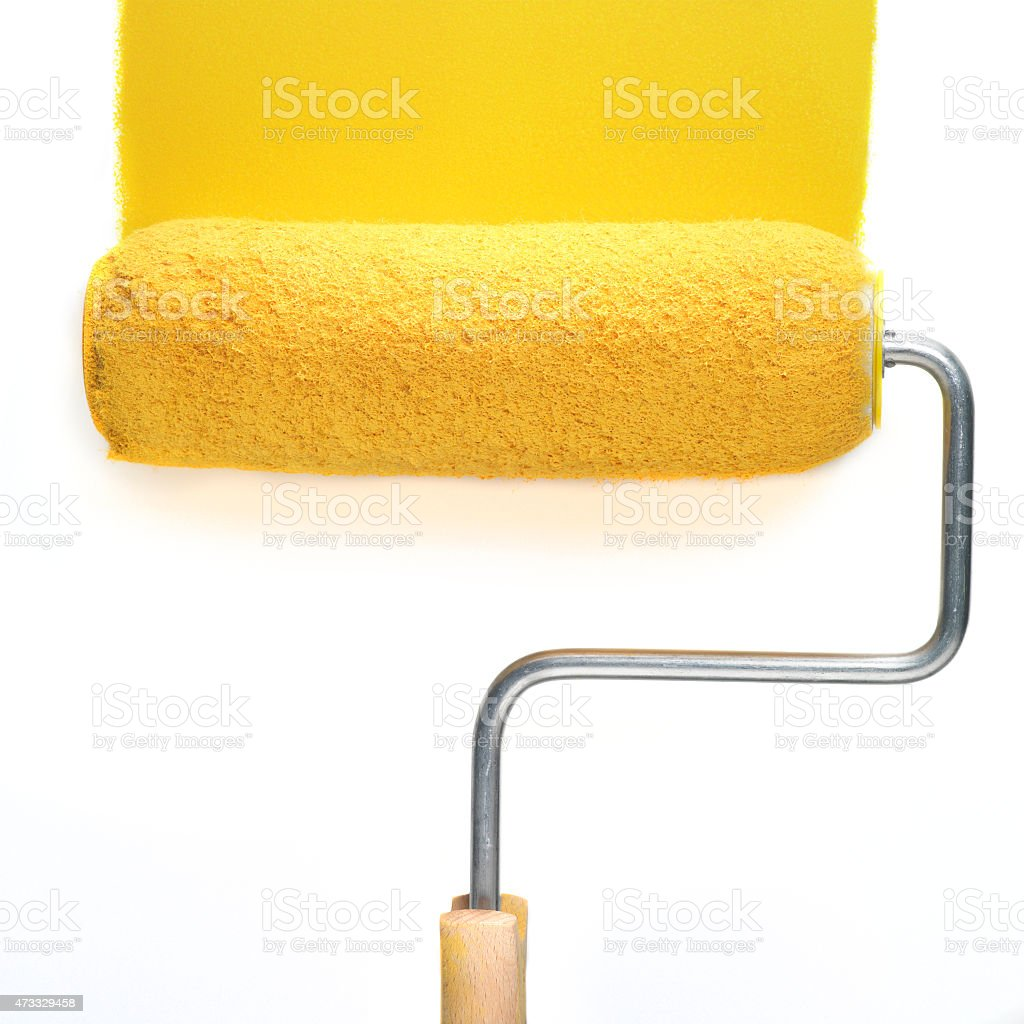 Paint roller with yellow paint stock photo