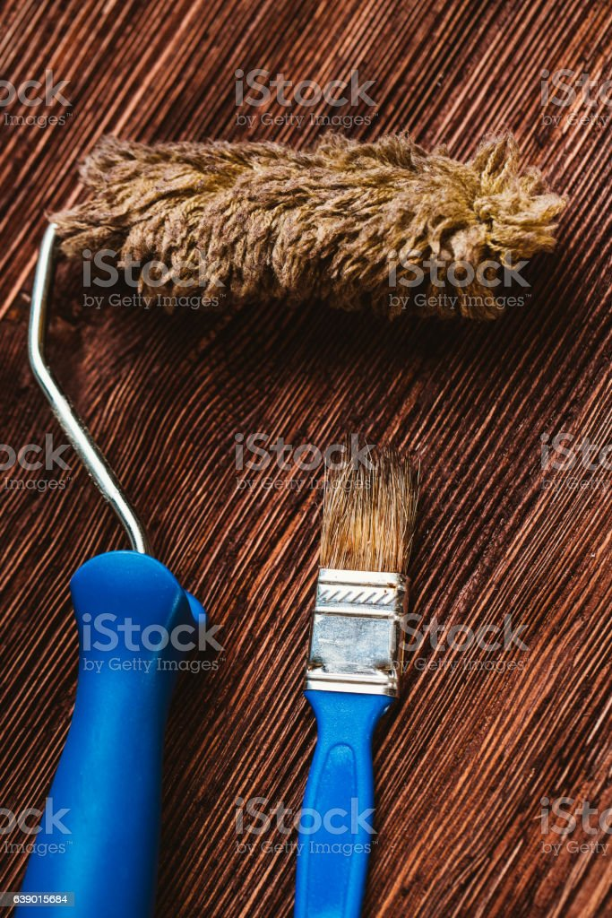 Paint rollers and brush on the dark wooden background stock photo