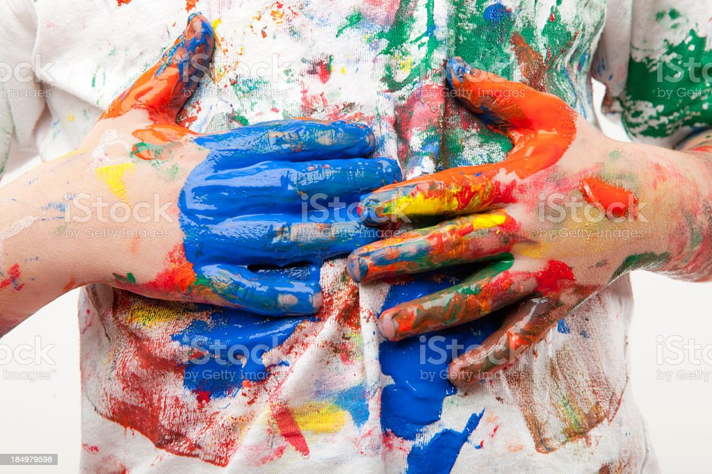 Paint soiled hands being wiped on a white shirt stock photo