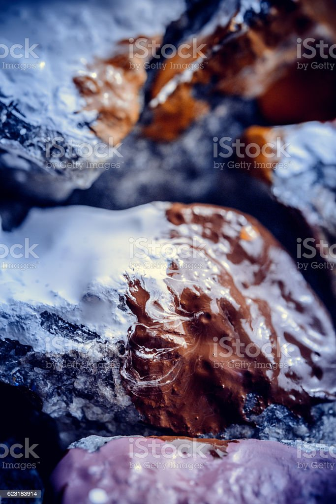 paint spreads on the surface of small stones stock photo