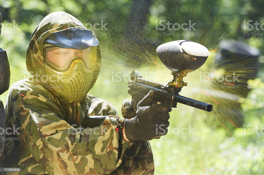 A paintball player being hit with a paintball stock photo