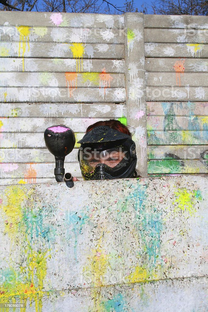 Paintball player hide behind paint-splattered wall stock photo
