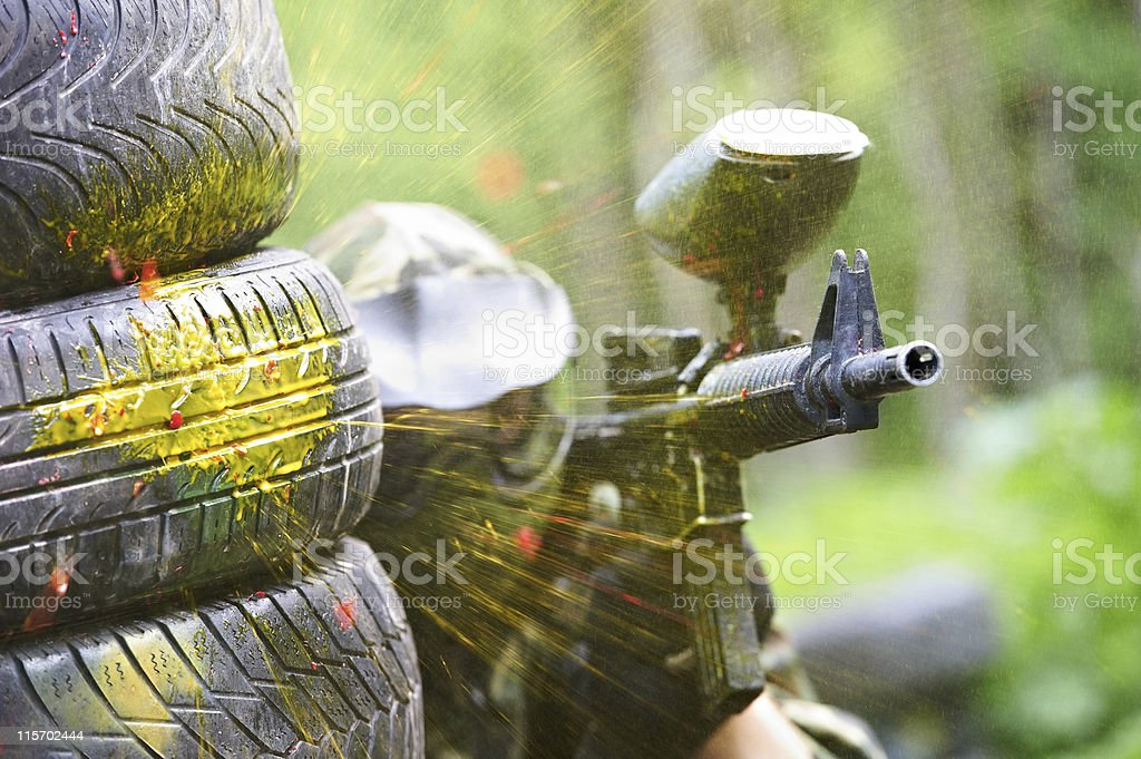 paintball player under gunfire stock photo