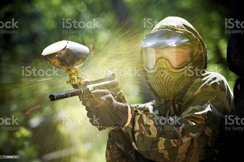 Paintball player with paint ball exploding on his gun stock photo