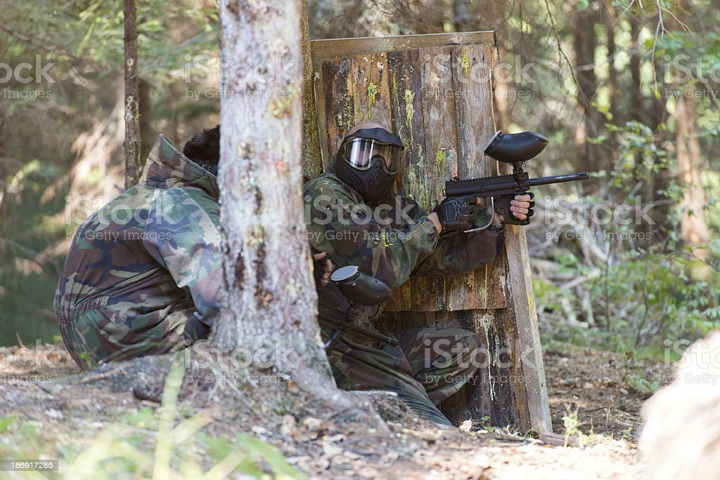 Paintball Players Hide Behind Tree royalty-free stock photo