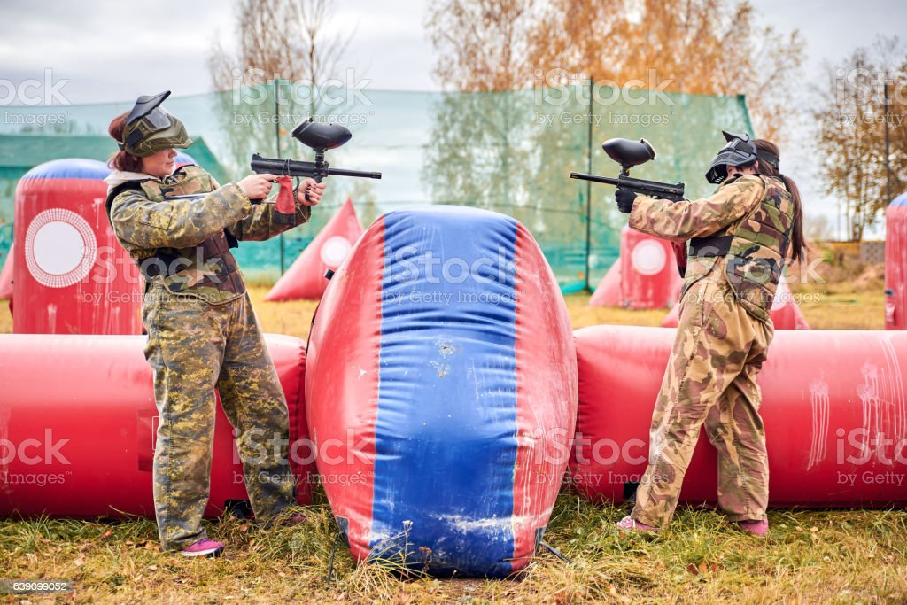 Paintball sport player girls in protective camouflage uniform stock photo
