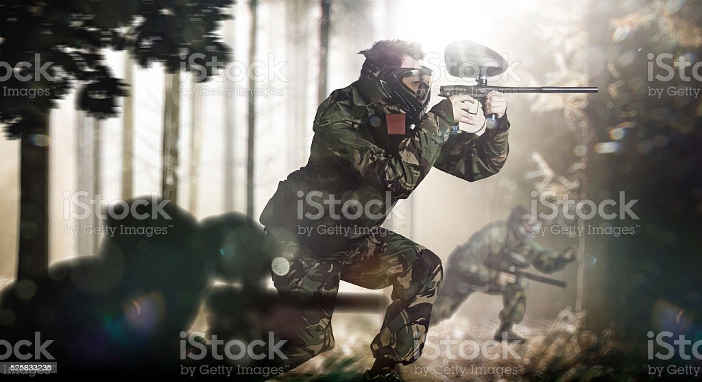 Paintball team in action forest location stock photo
