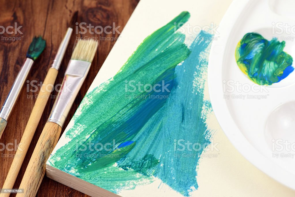 paintbrush and canvas with green paintings on table stock photo