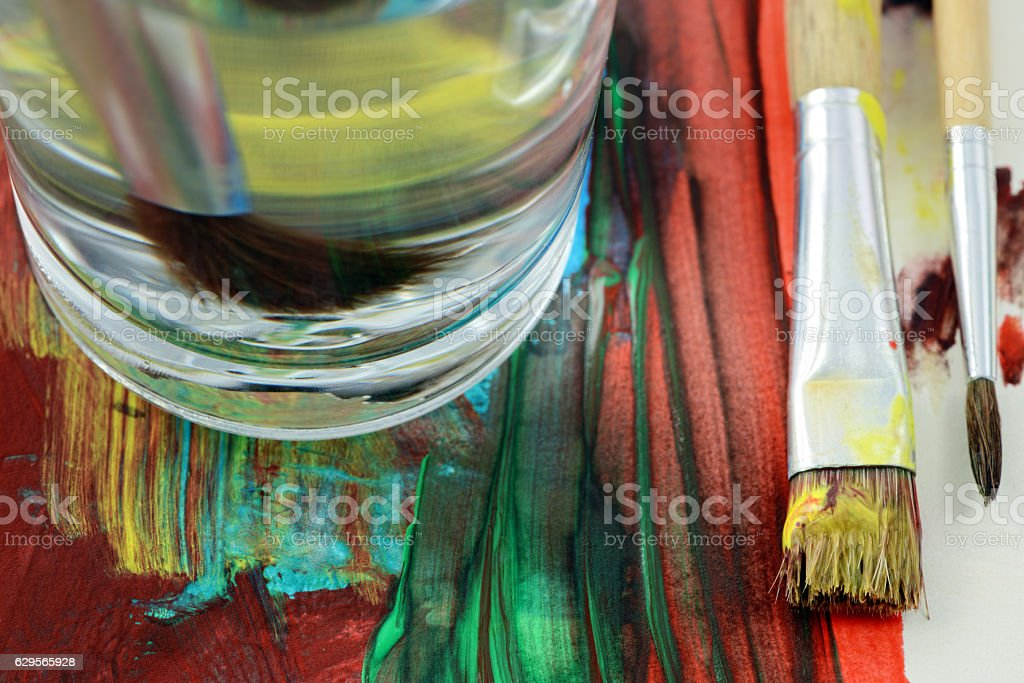 paintbrush and canvas with paintings on table stock photo