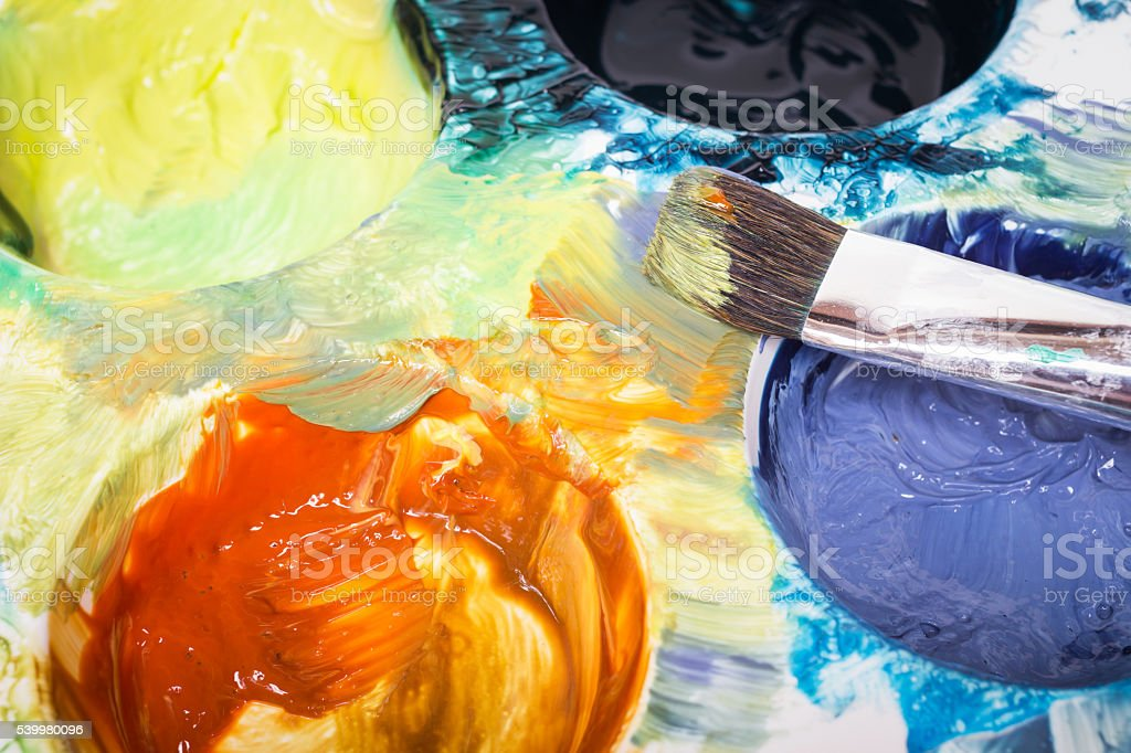 Paintbrush and messy palette with watercolor paints stock photo