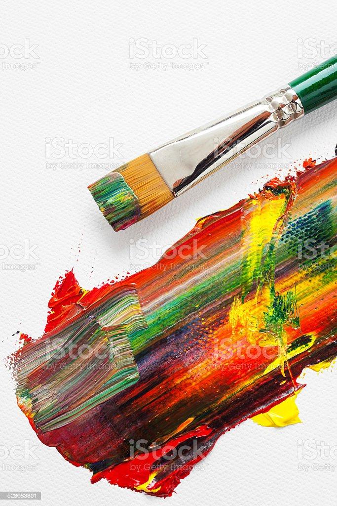 Paintbrush and mixed rainbow oil paints on artist canvas stock photo