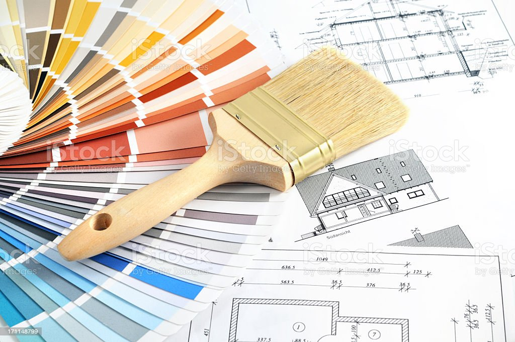A paintbrush and paint swatches laying on design blueprints  stock photo
