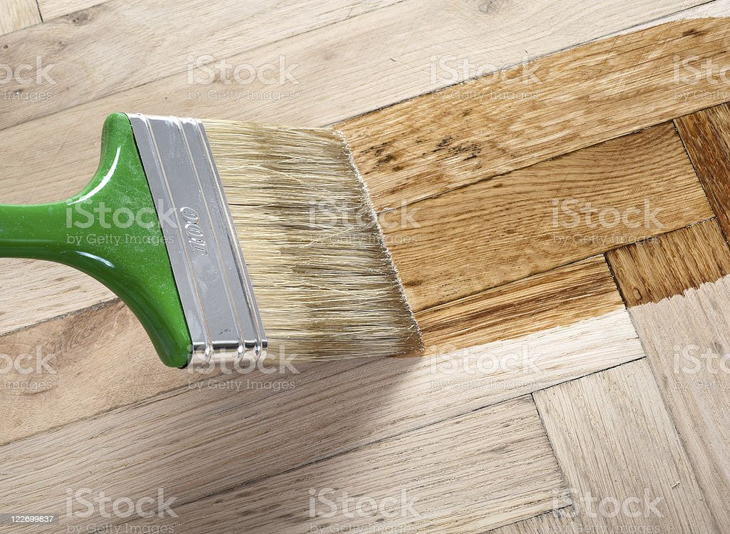 A paintbrush applying varnish to a wooden floor stock photo