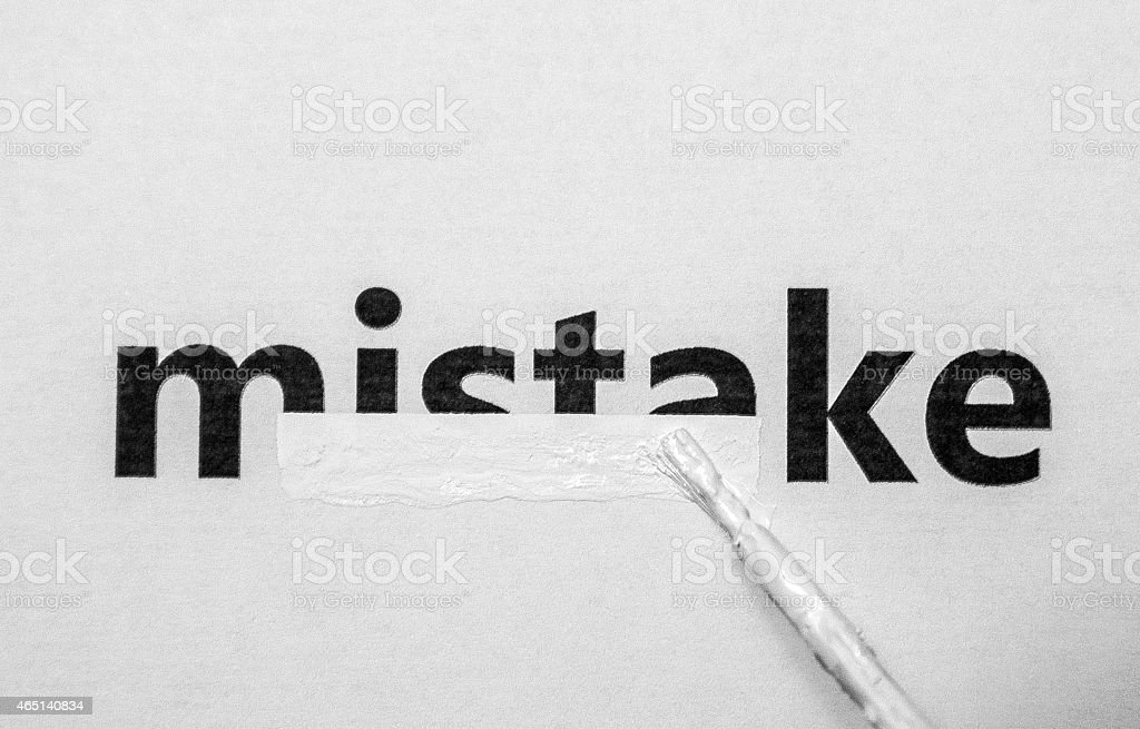 A paintbrush covering up mistake with white paint stock photo