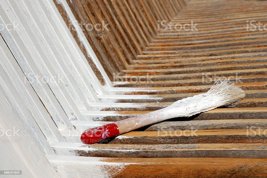 paintbrush on a freshly painted wooden bench stock photo