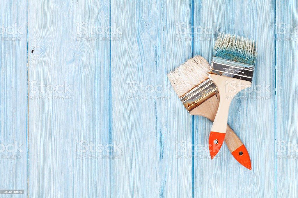 Paintbrush over blue wood stock photo