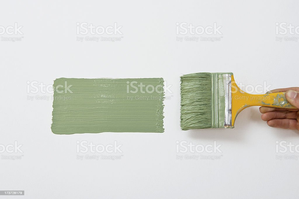 Paintbrush painting wall into green royalty-free stock photo